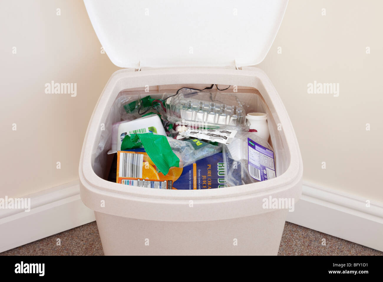 Plastic waste bin full of household rubbish with lid open. England, UK, Britain - Stock Image