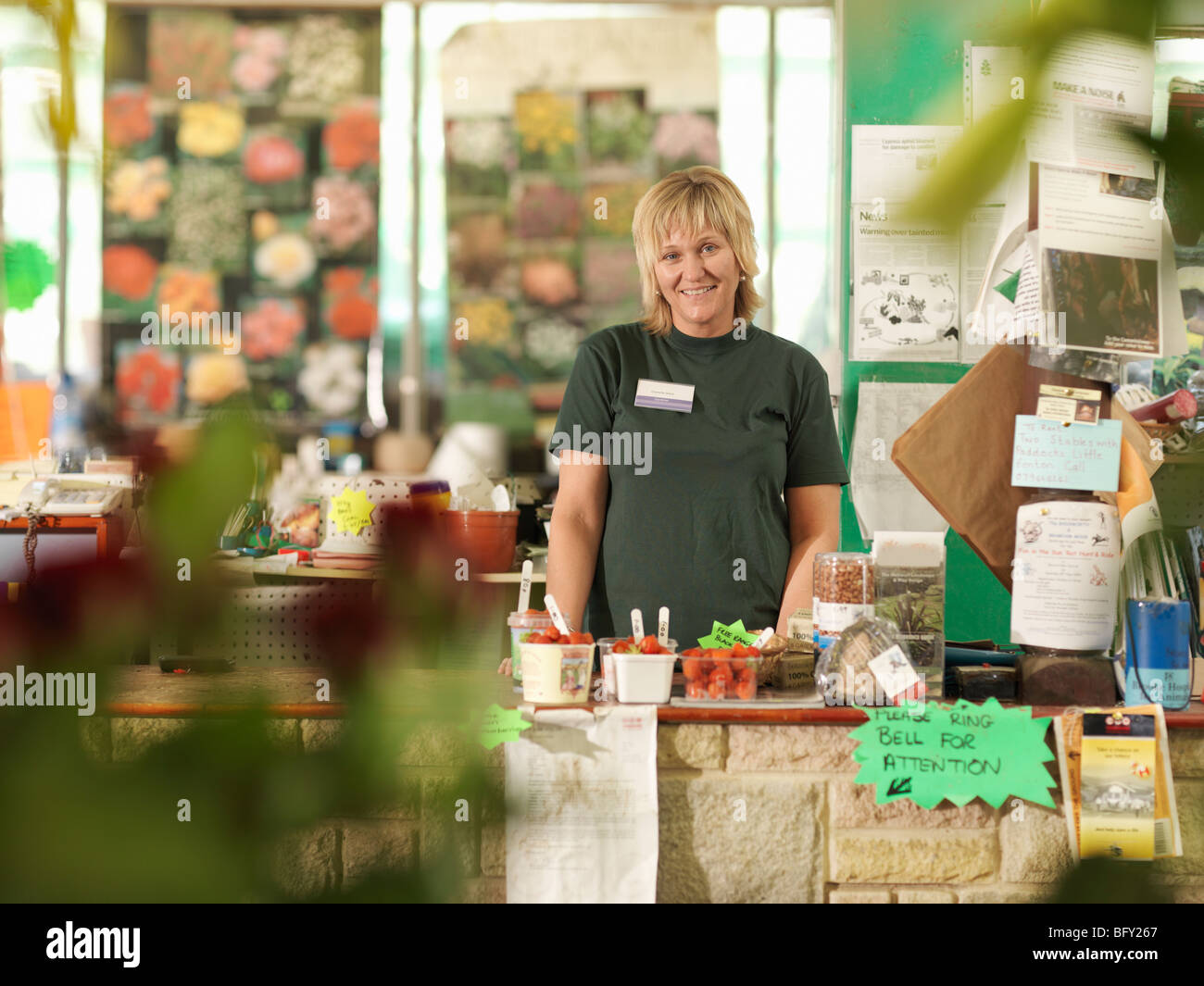 Female Garden Center Worker Behind Till - Stock Image