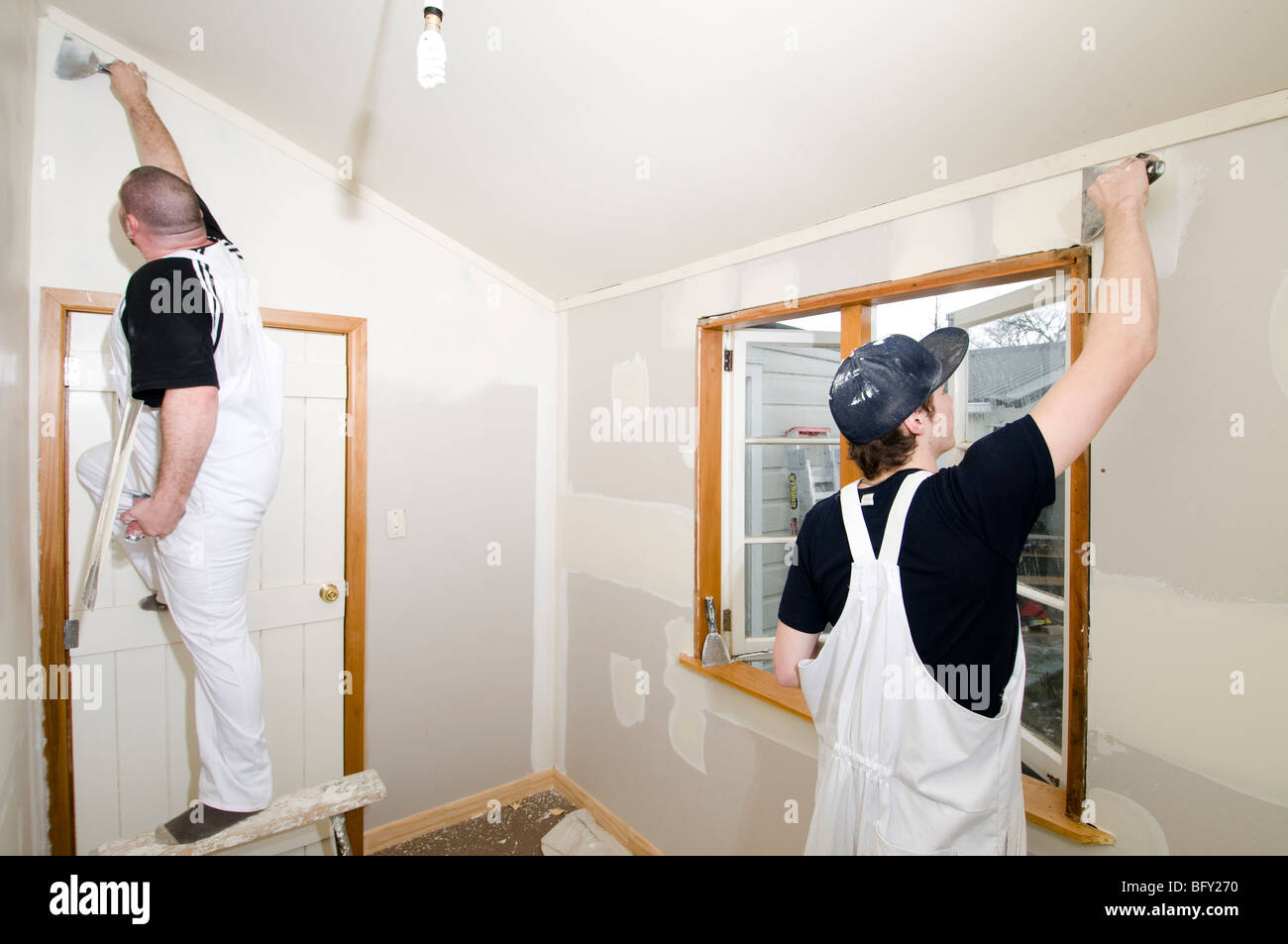Man and apprentice plastering room Stock Photo