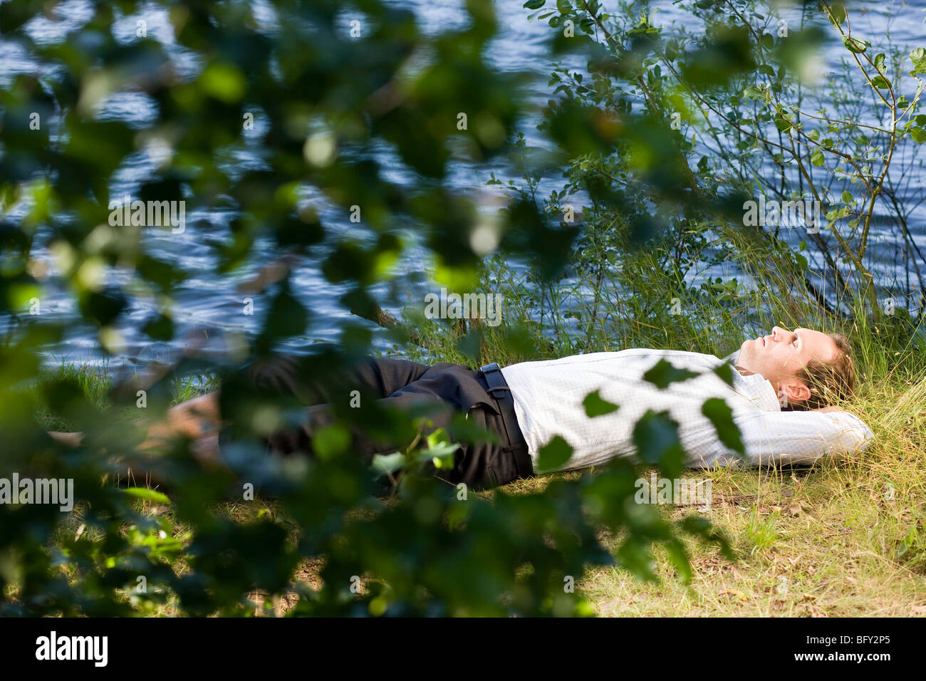businessman relaxing on lakefront - Stock Image