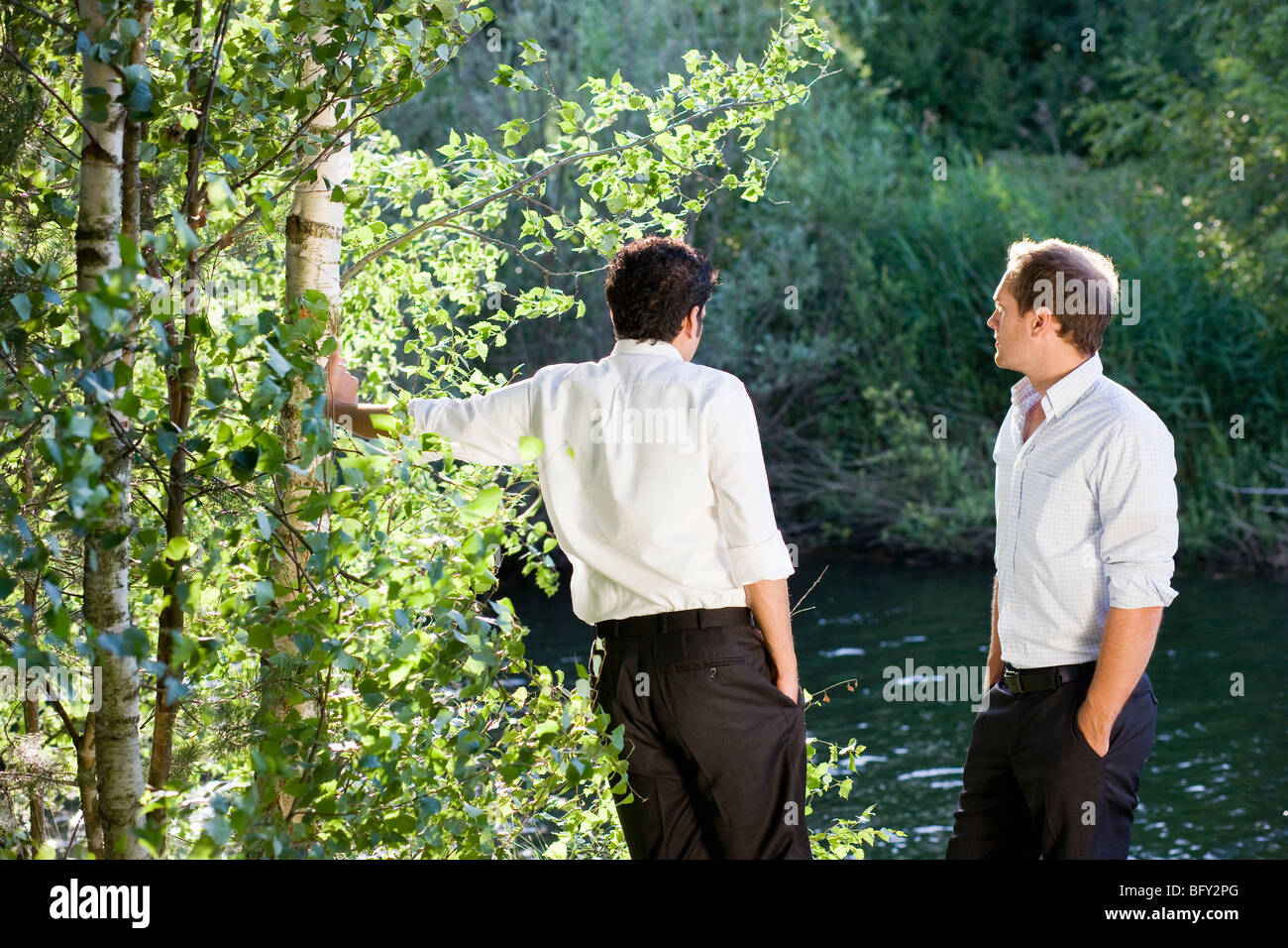 two businessmen talking on lakefront - Stock Image