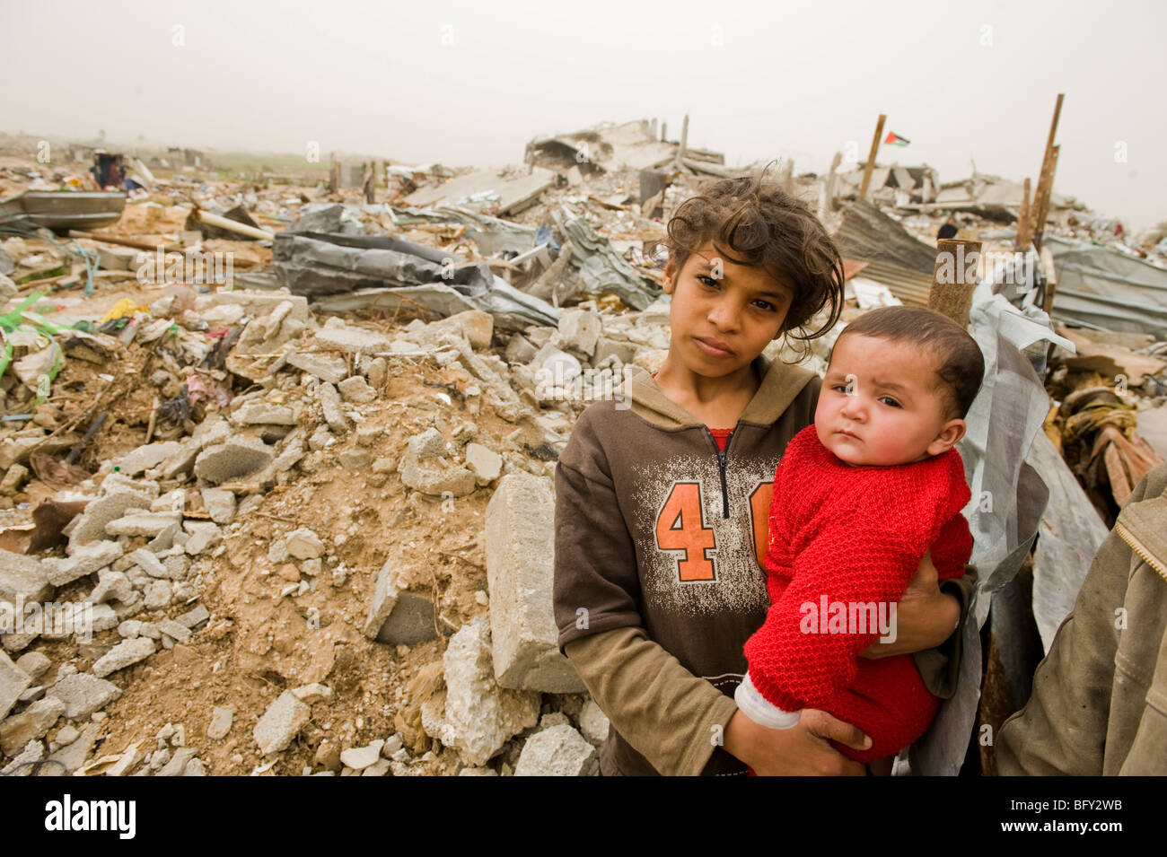 Children at the remains of their home destroyed in January's Israeli military offensive, in Jebaliya, northern - Stock Image