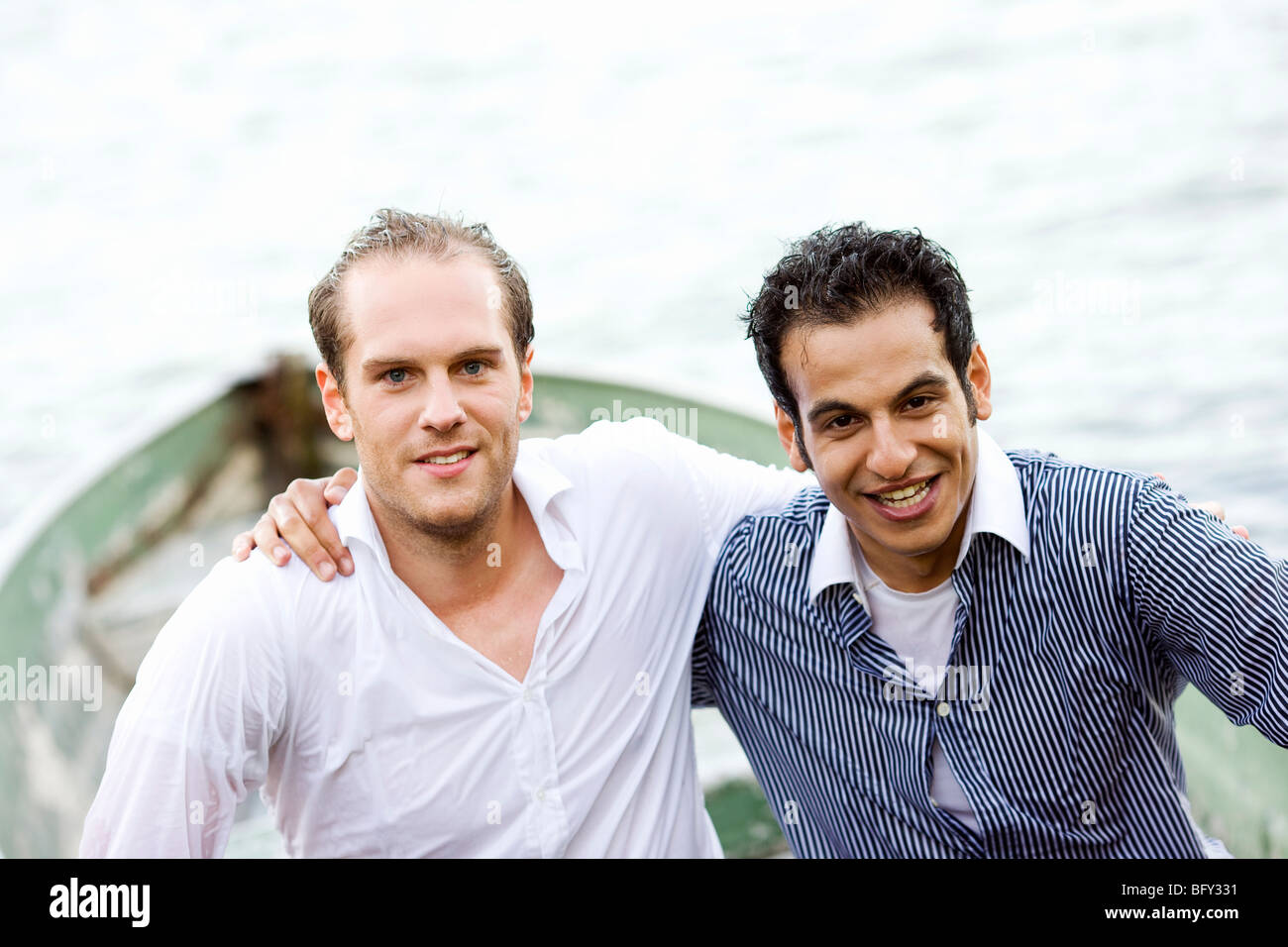 two businessmen sitting wet in rowboat - Stock Image