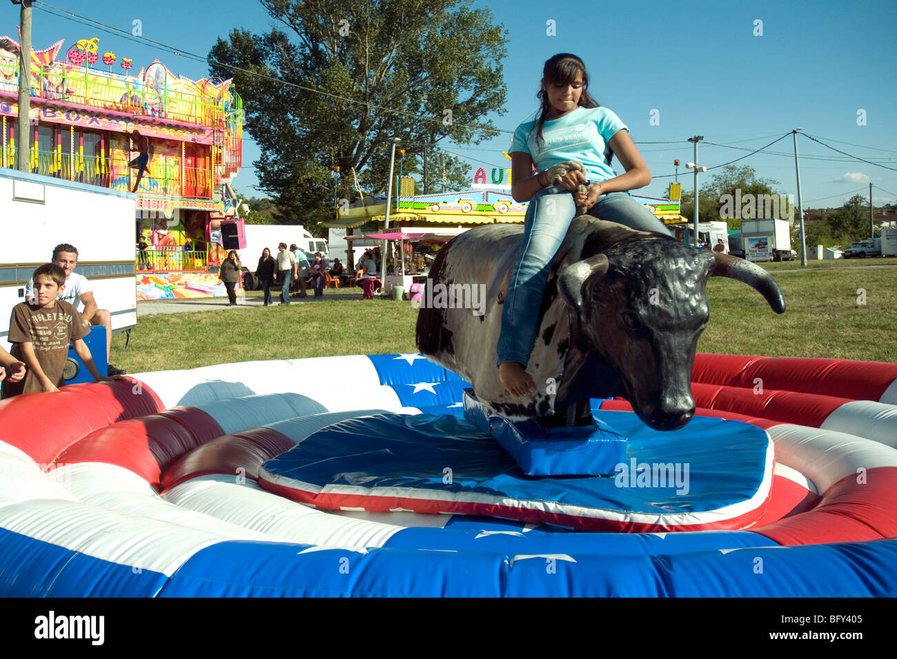 Rodeo style, a leggy cowgirl maintains her grip on the mechanical bull at a Gascon fair in Auch Stock Photo