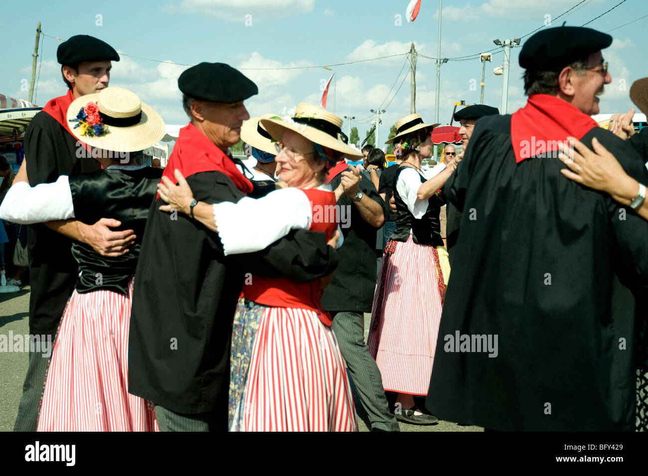 Sedate folk dancers in Gascon trad costume entertain visitors to the Gascogne Expo fairground in Auch - Stock Image