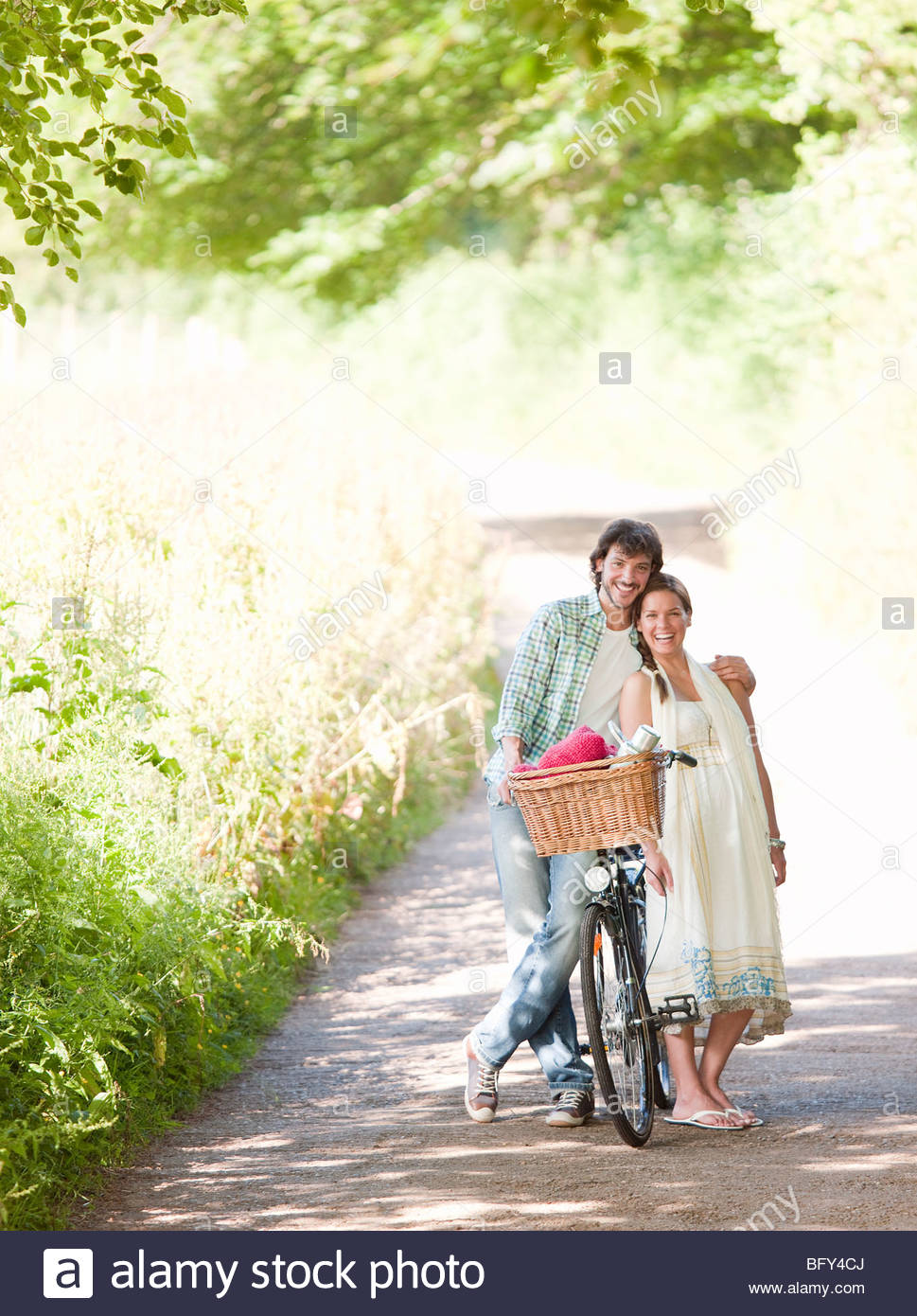 Man and woman with bike in country lane - Stock Image
