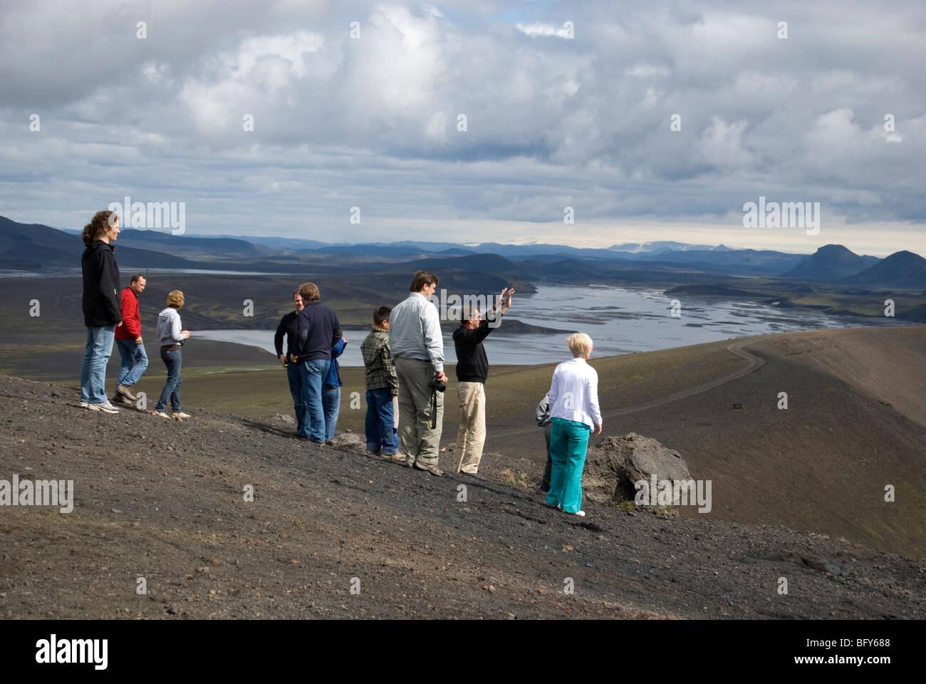 Tourists enjoying the volcanic landscape, Iceland - Stock Image