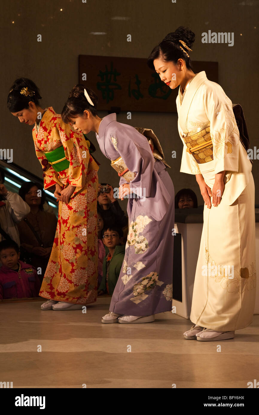 Japanese Women Bowing at Kimono Show at Nishijin Textiles - Stock Image