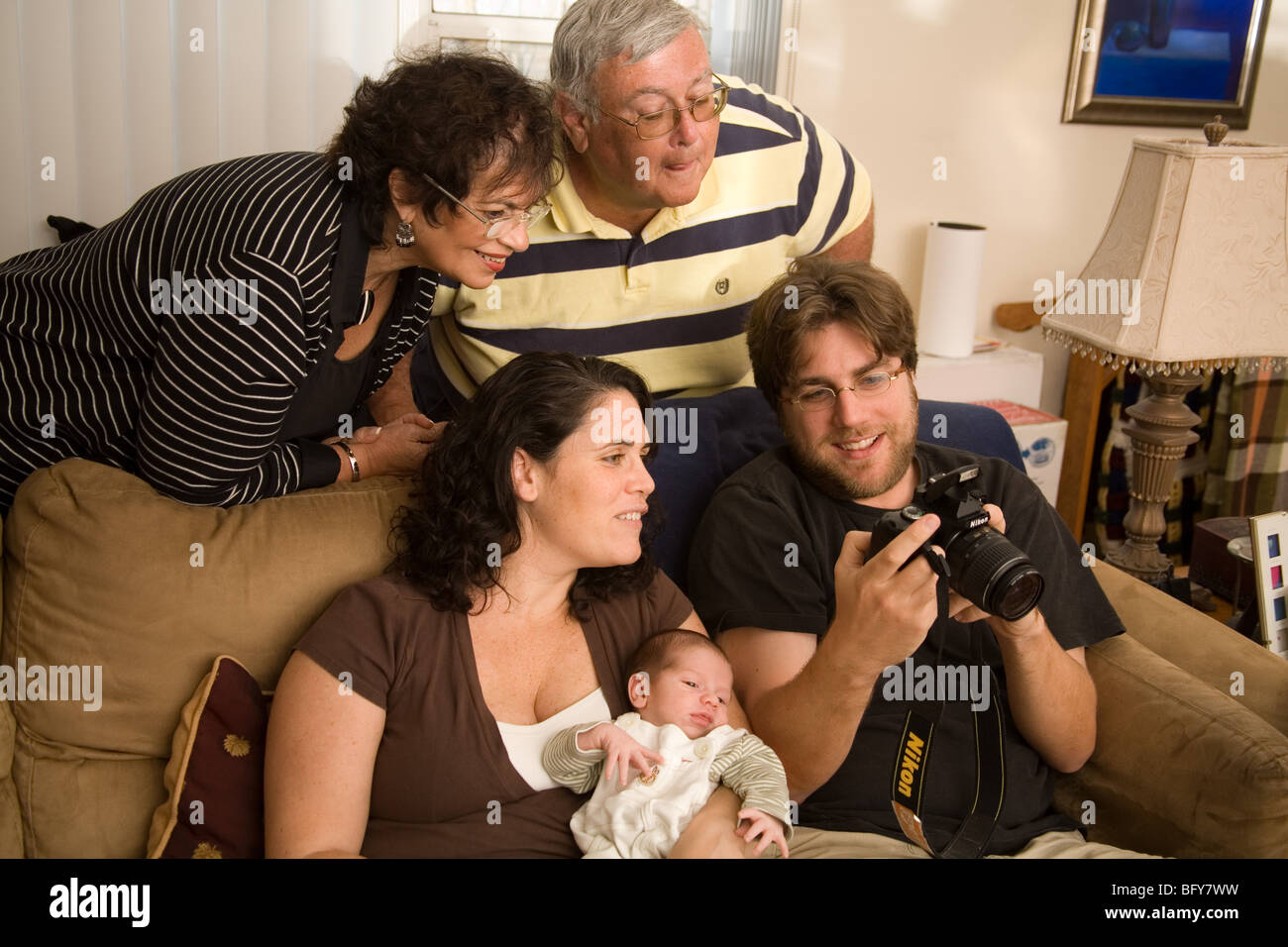 A young couple on a sofa holding a baby and her parents all look at a photo on the back of a digital SLR camera - Stock Image