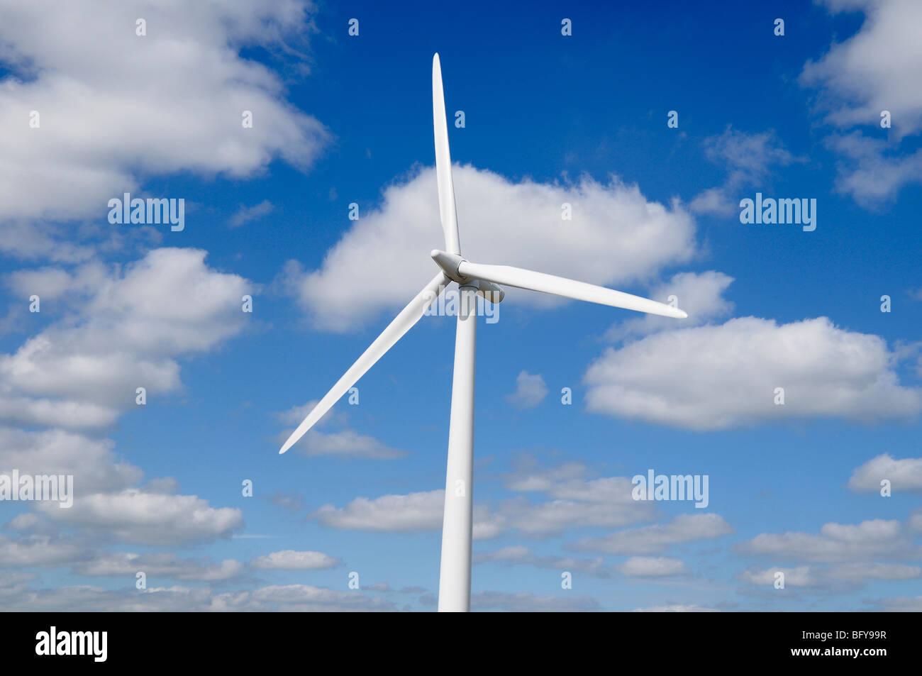 Wind Turbine Against a Cloud Filled Blue Sky - Stock Image