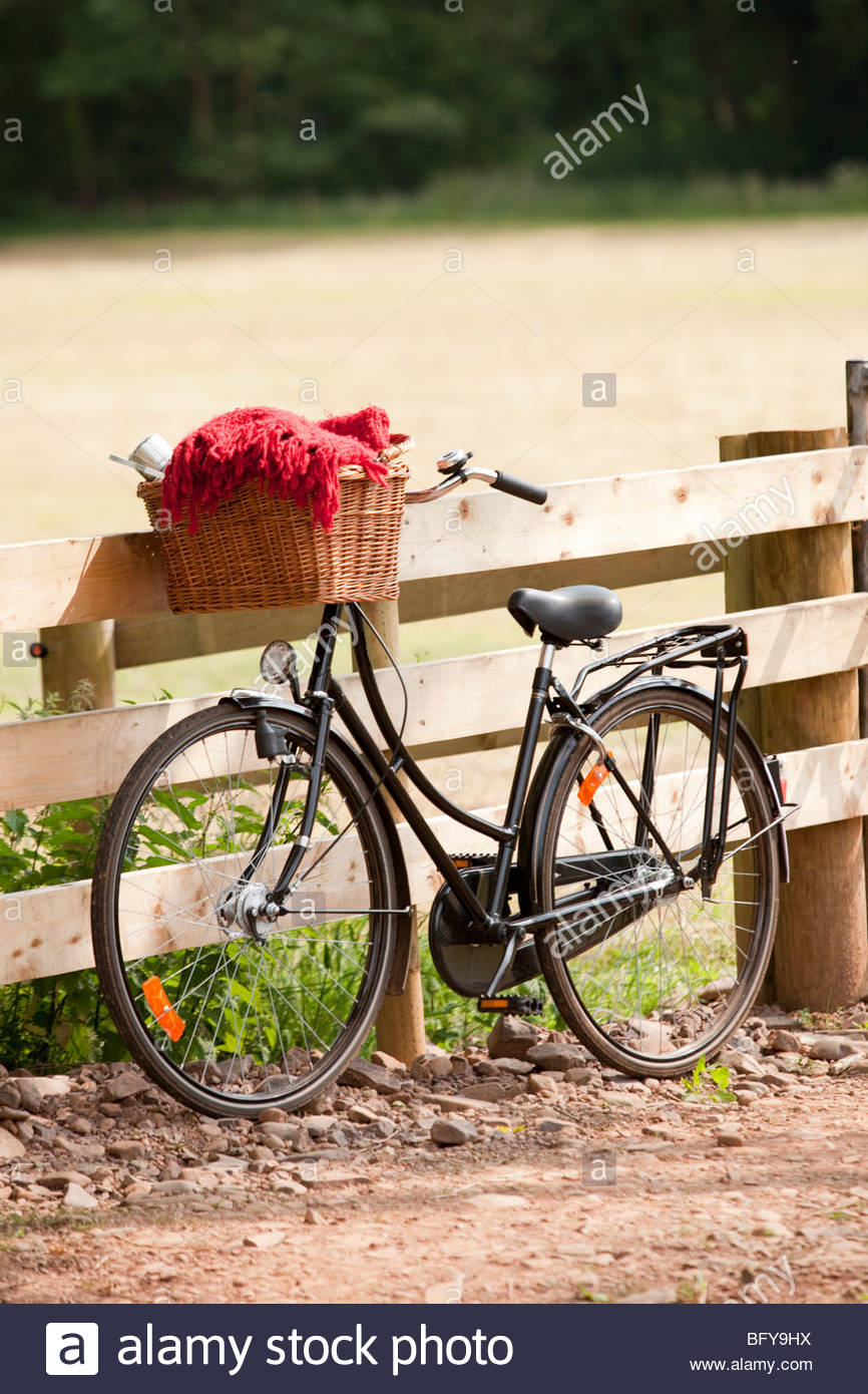 Bicycle leaning against country fence - Stock Image