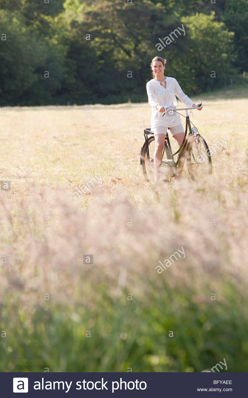 Woman on bicycle in countryside - Stock Image