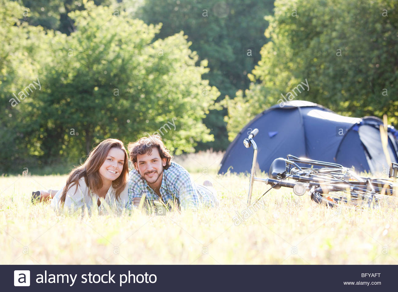 Couple laying in grass in country scene - Stock Image