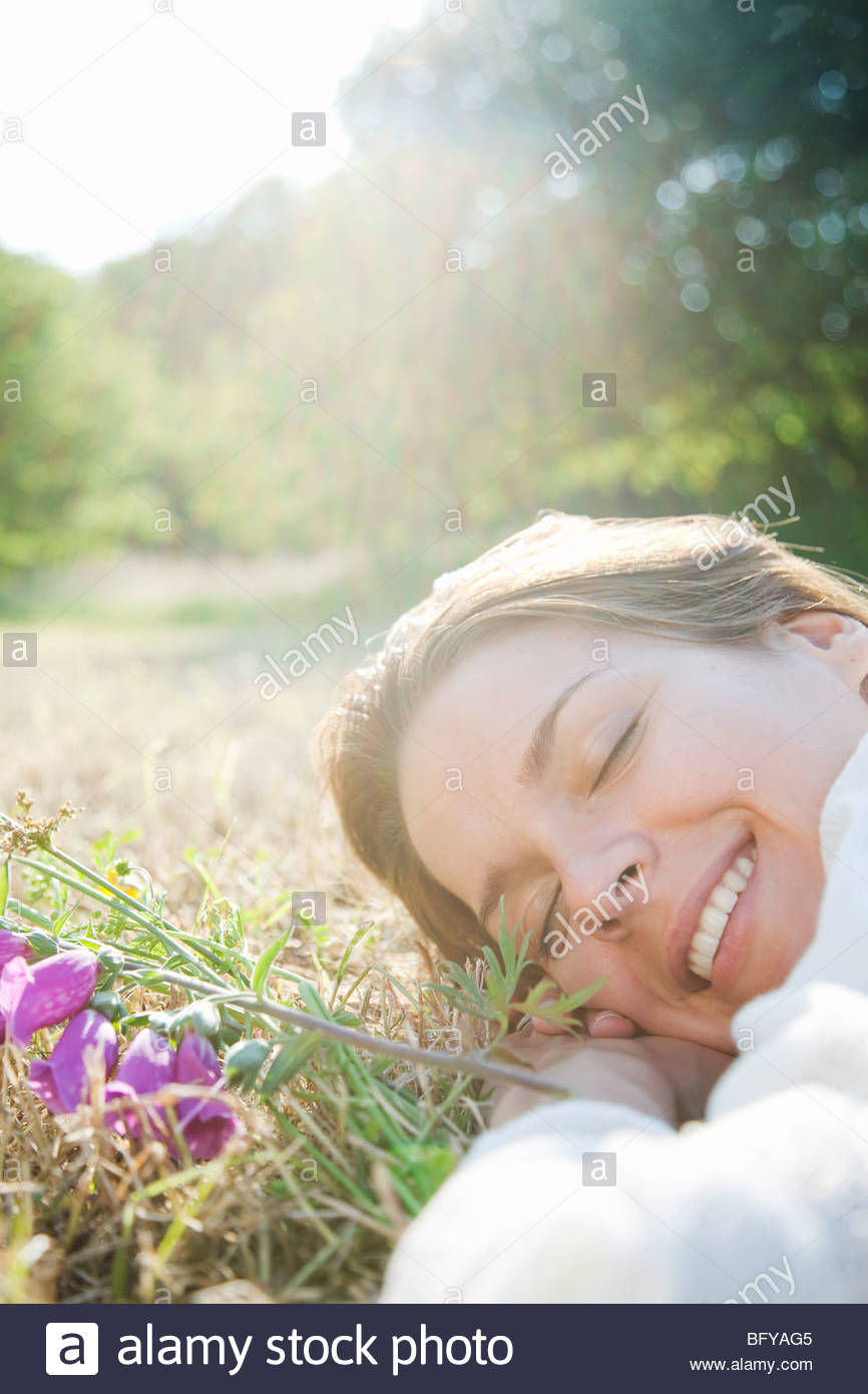 Woman lying in grass with flowers Stock Photo