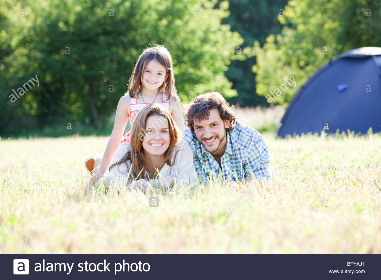 Family laying in grass in country scene - Stock Image