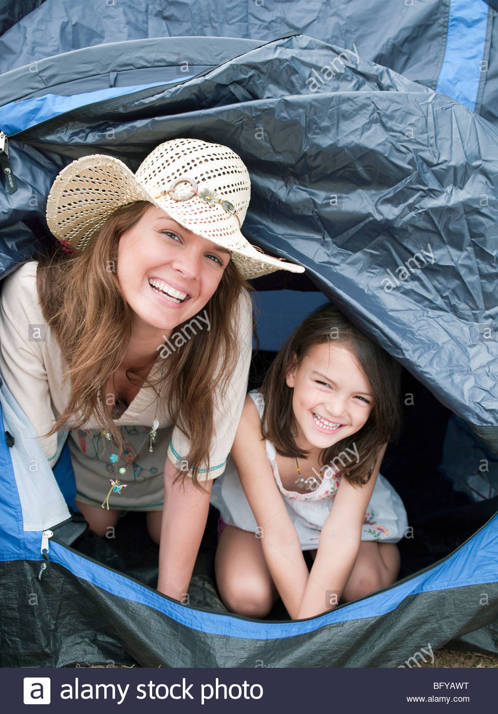 Mother and child emerging from tent - Stock Image
