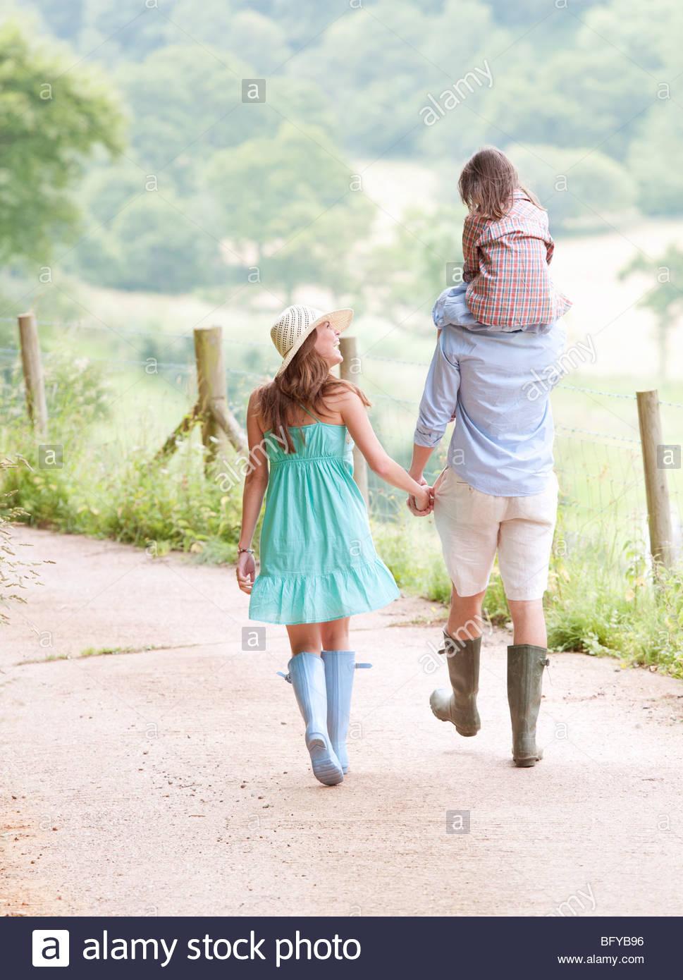 Family walking together on lane - Stock Image