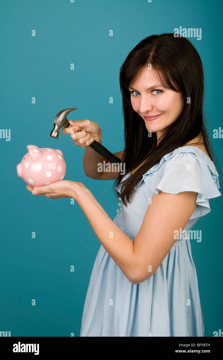 Woman holding hammer over piggy bank - Stock Image