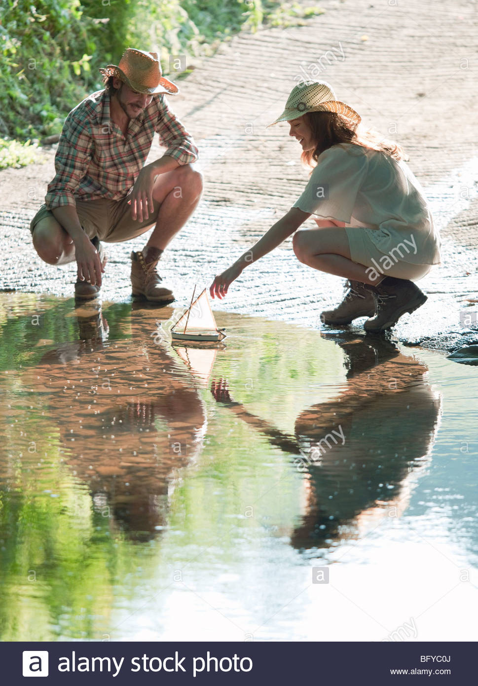 Man and woman with model boat on lake - Stock Image
