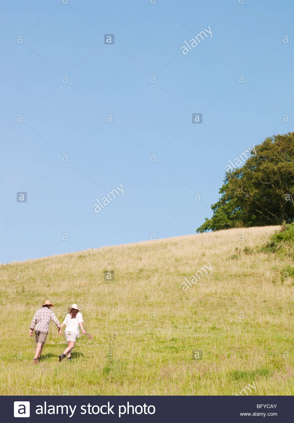 Man and woman walking up hill - Stock Image