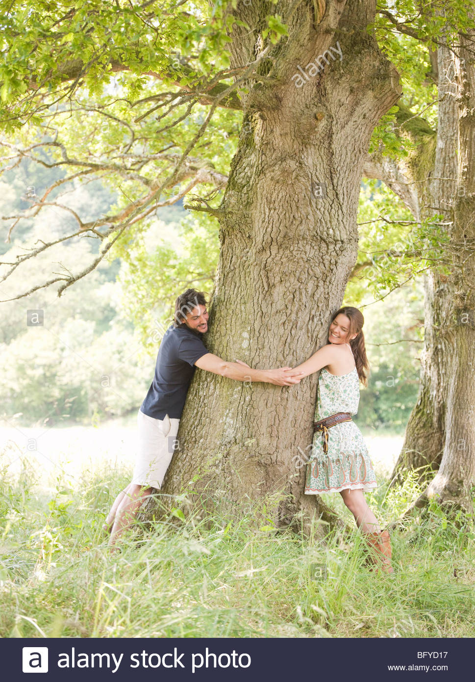 couple with arms around tree - Stock Image