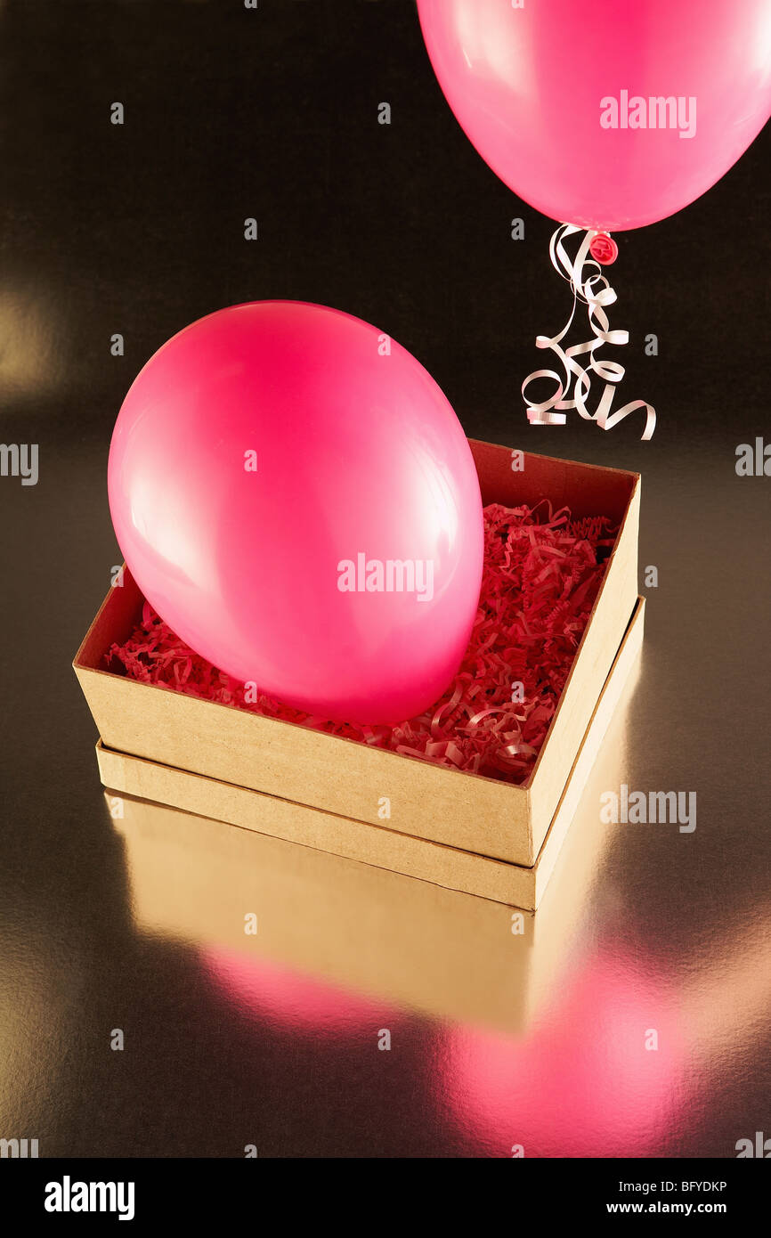 Cardboard box with pink party balloons Stock Photo