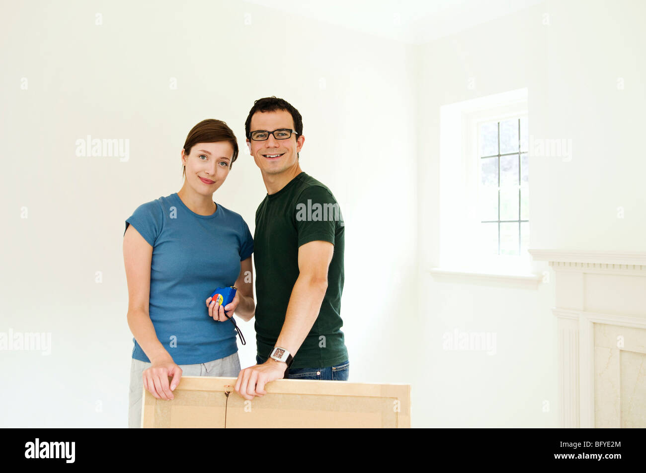 A couple putting up a picture. - Stock Image