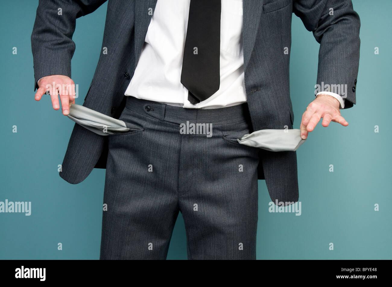Businessman holding empty pockets - Stock Image