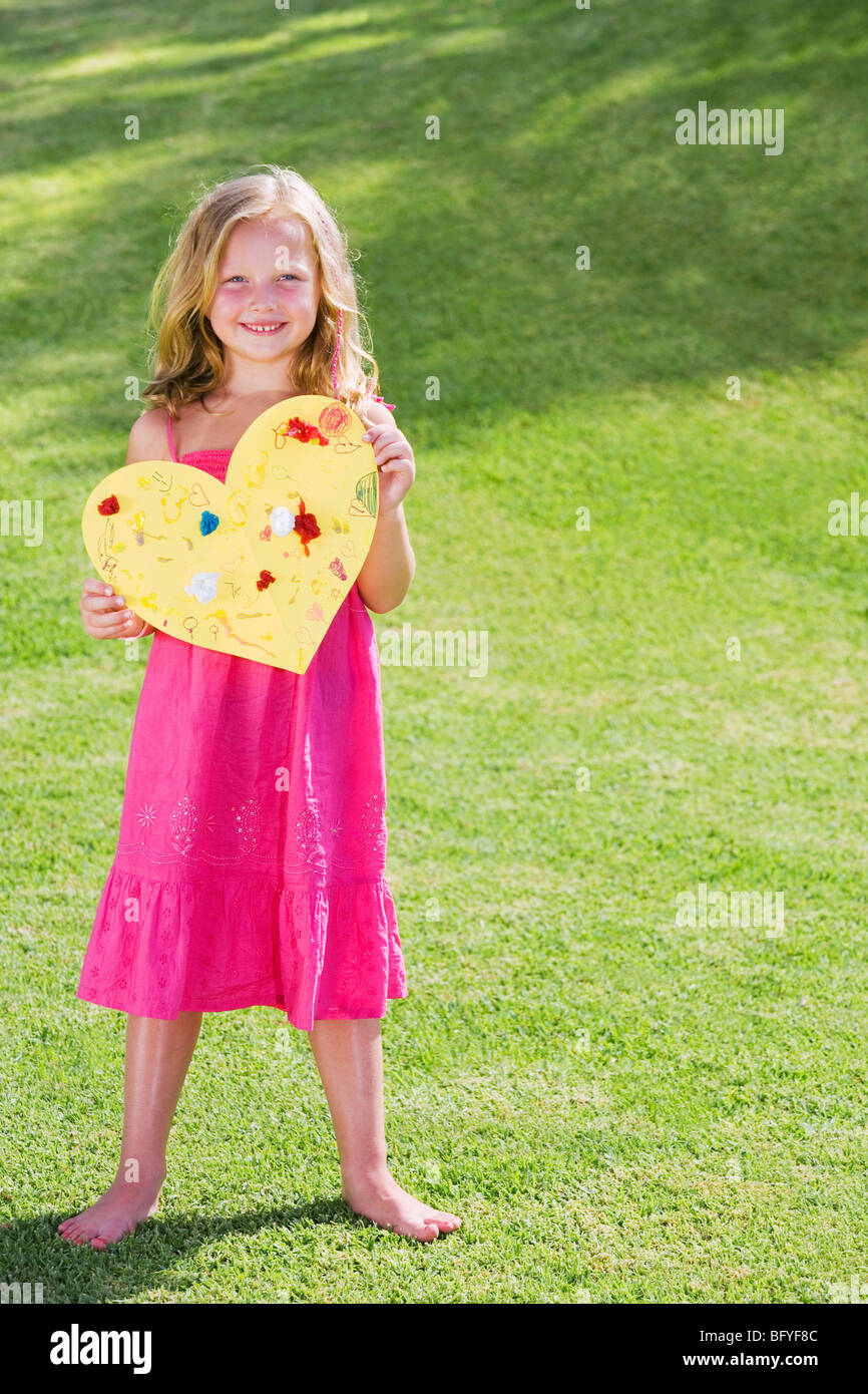 Young girl holding paper heart - Stock Image