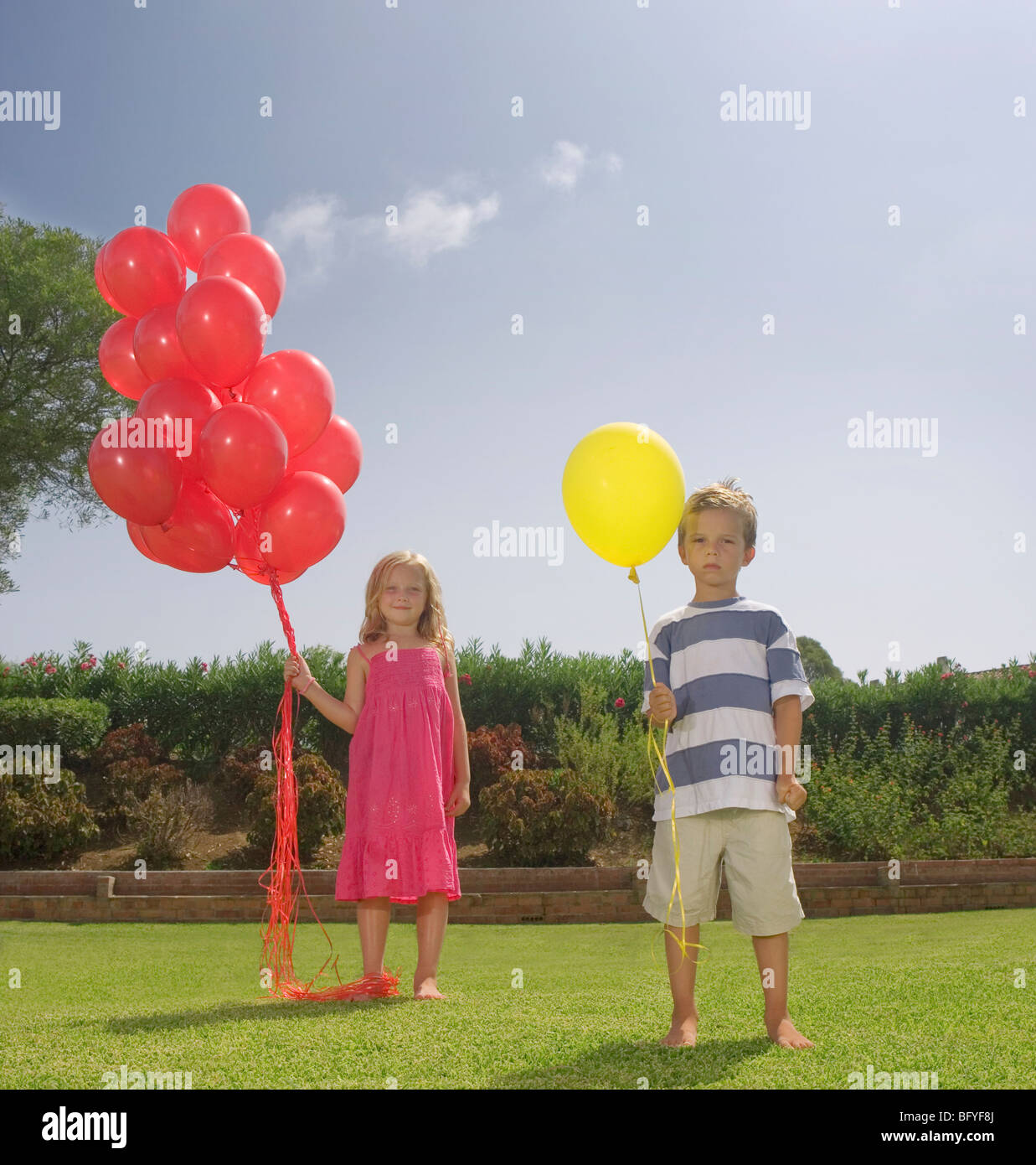 Young children holding red balloons - Stock Image