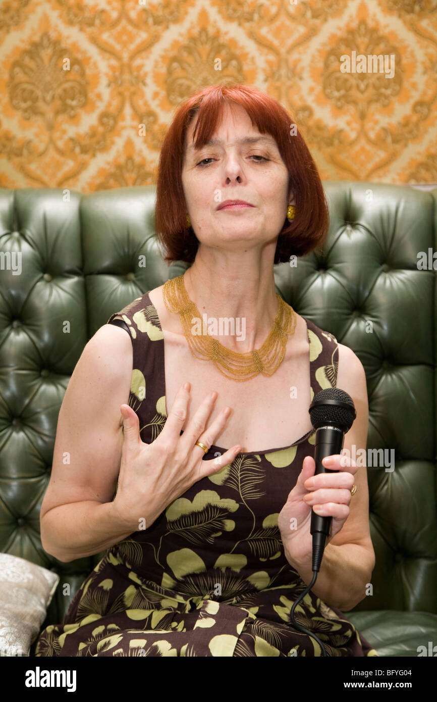 Mature lady singing at home Stock Photo