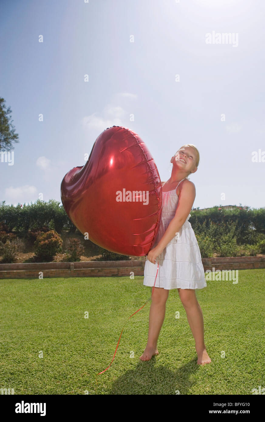 Young girl holding big red heart balloon Stock Photo