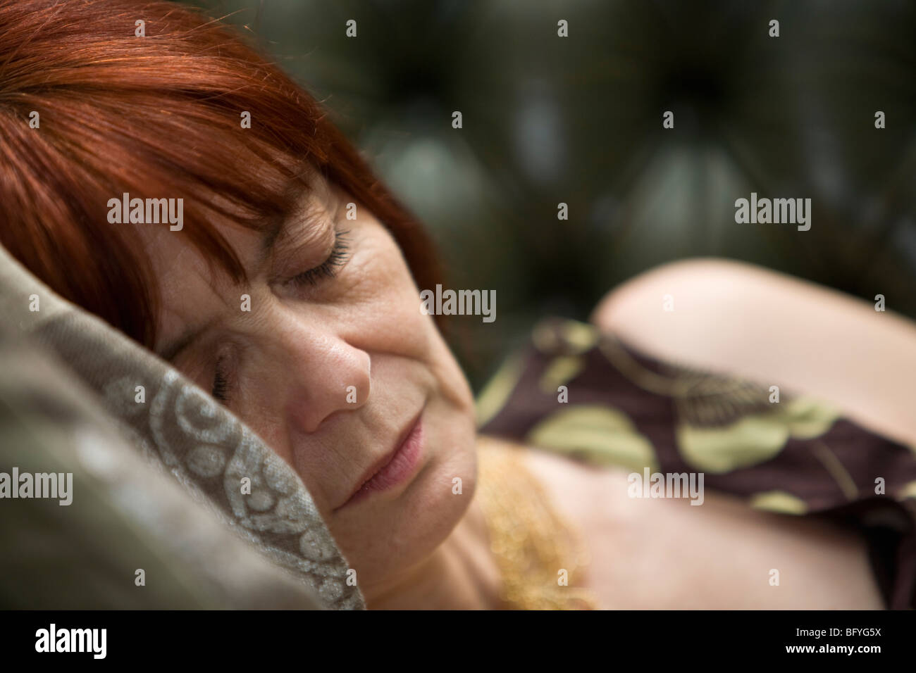 Mature lady Sleeping on couch - Stock Image