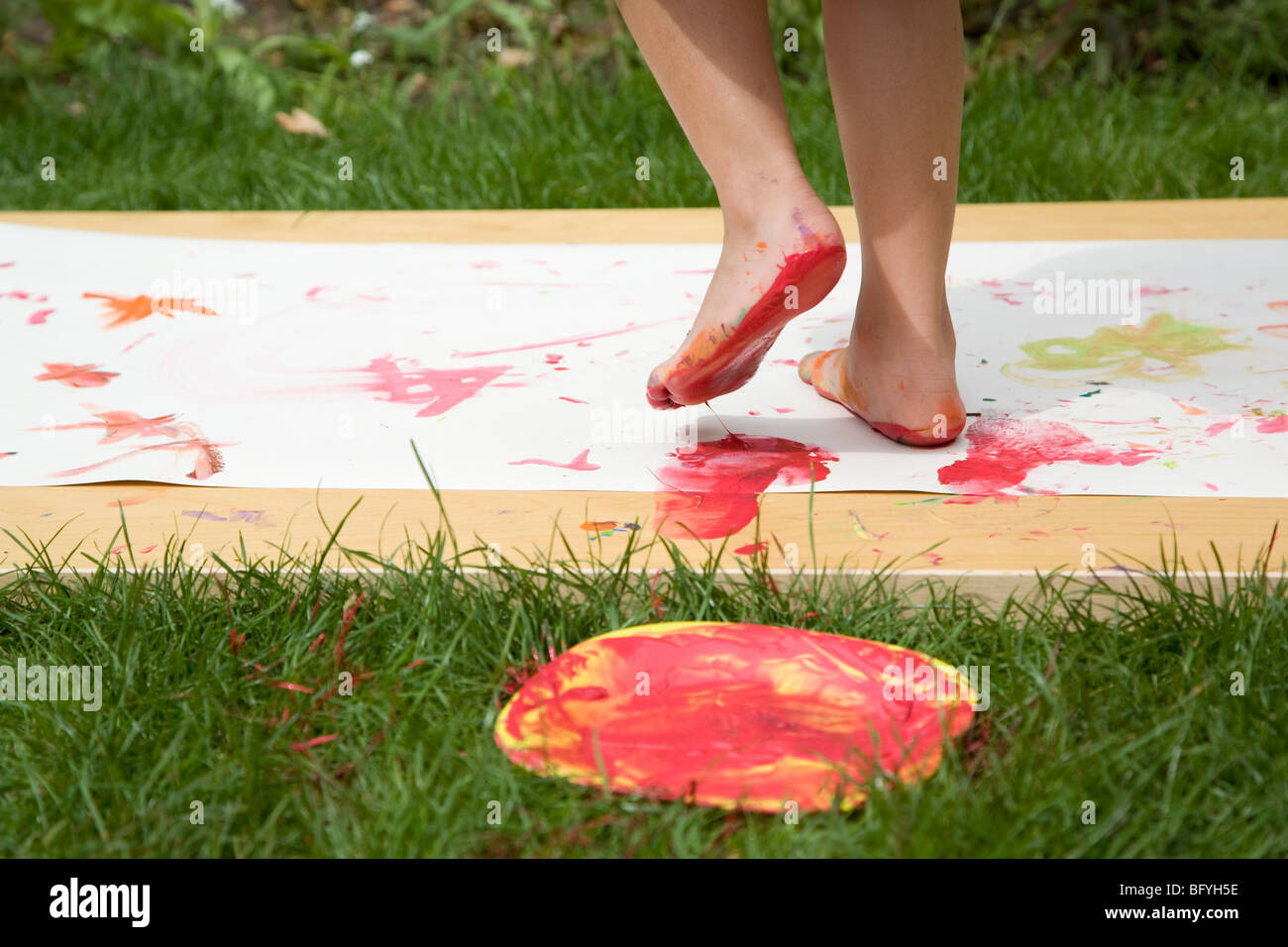 Child feet painting in the garden - Stock Image