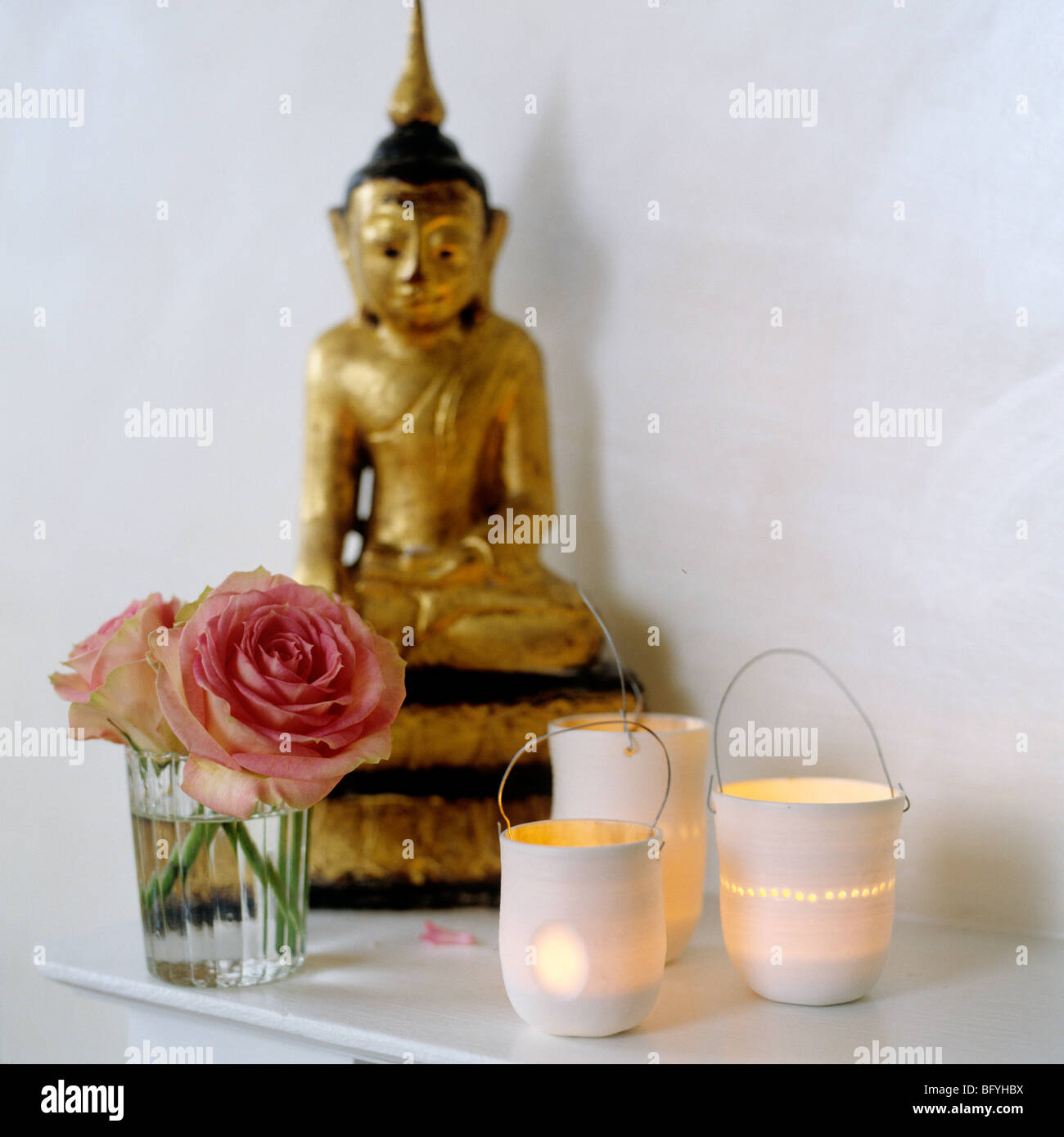 Golden Buddha statue, pink roses and candles on a shelf Stock Photo