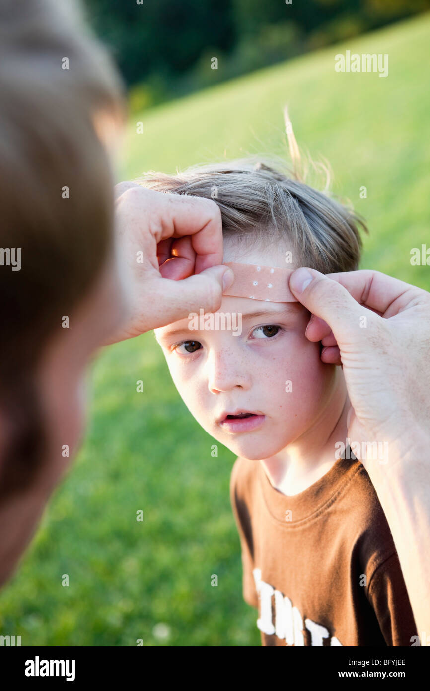 Father Applying Bandage to Son's Head - Stock Image