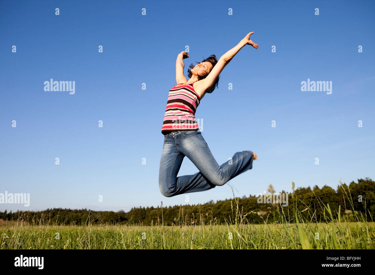 Woman Jumping On Meadow Stock Photo