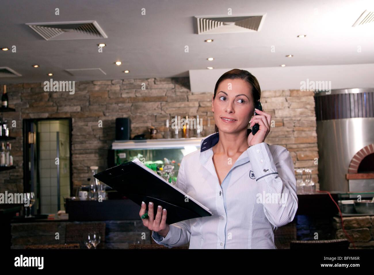 restaurant owner taking reservation on mobile phone - Stock Image
