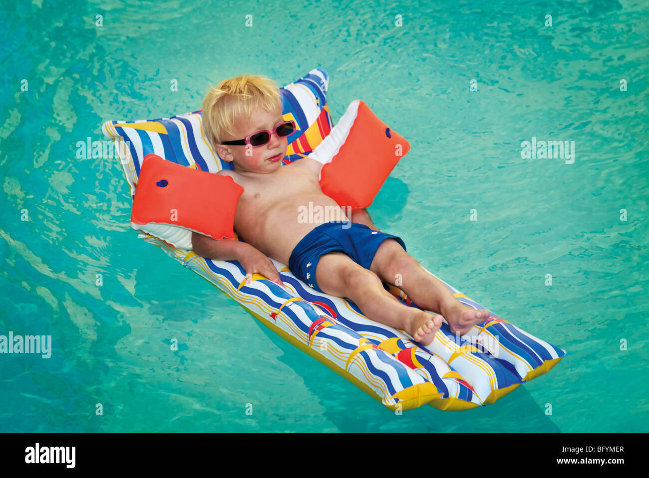 young boy lying on air bed floating in swimming pool BFYMER