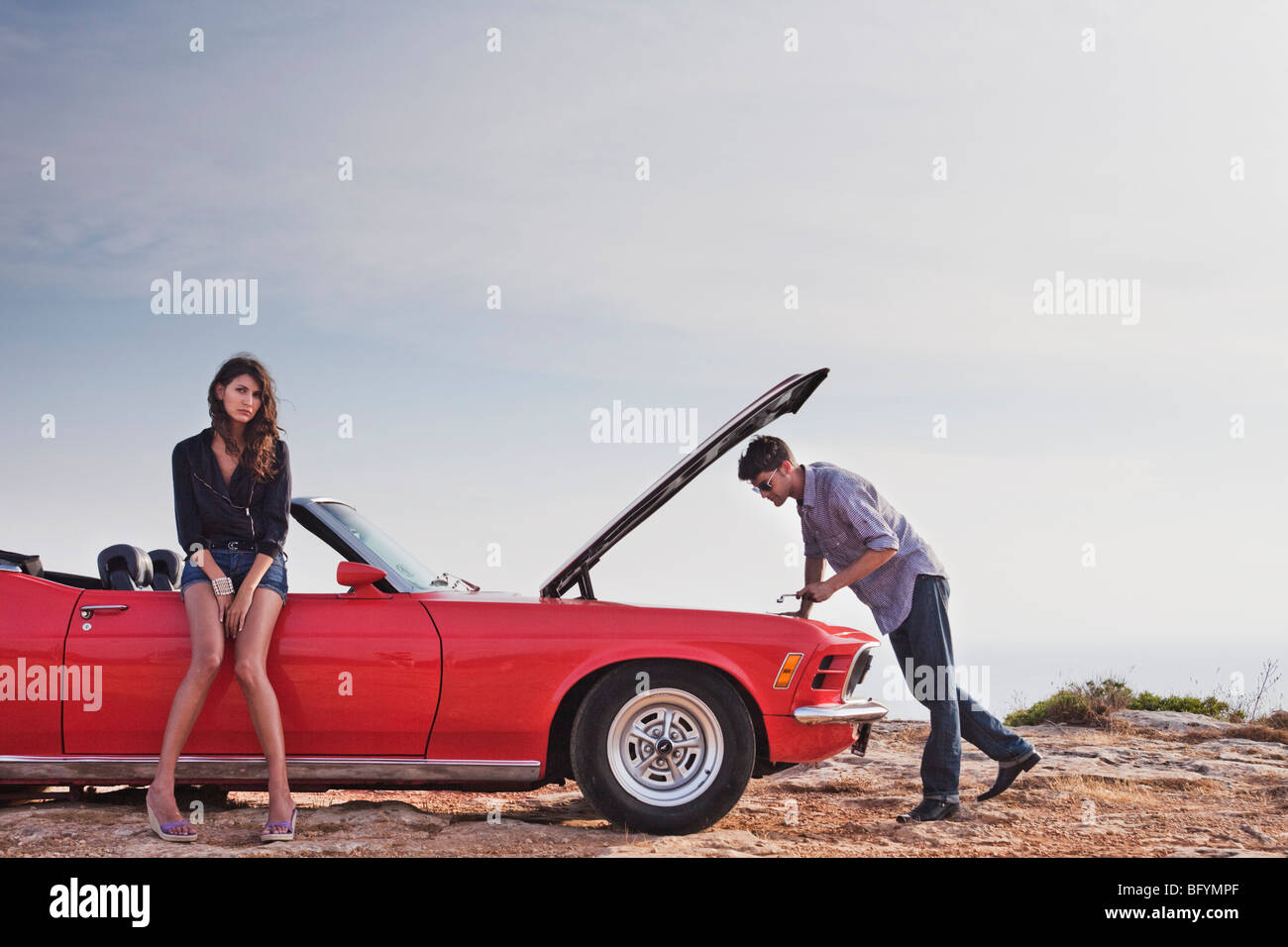 couple standing at car with opened hood - Stock Image