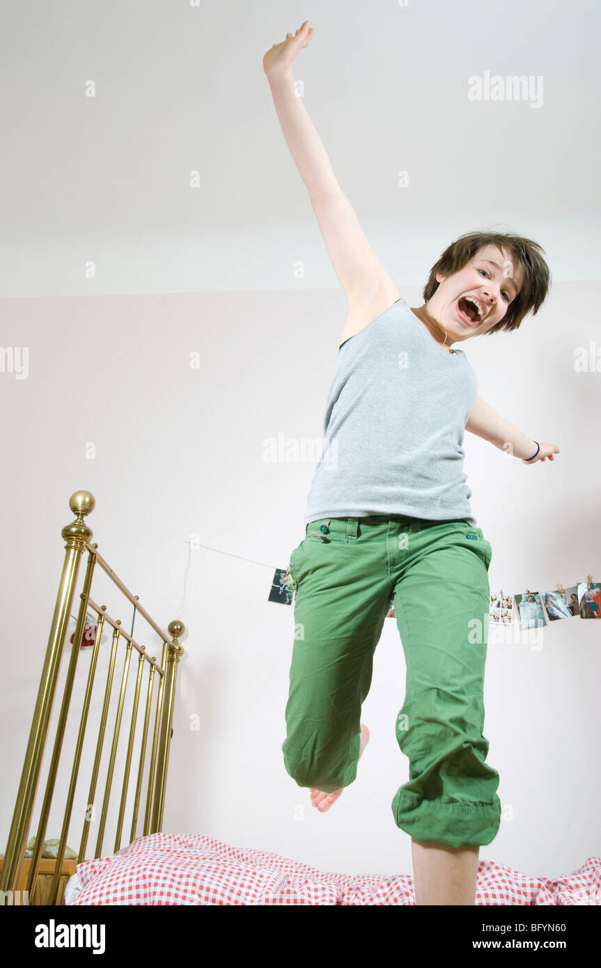 teenage girl jumping on bed - Stock Image
