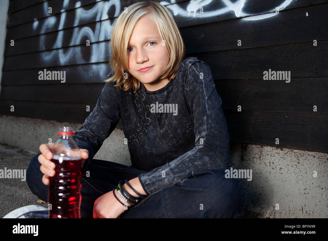 portrait of blond young boy with plastic bottle - Stock Image