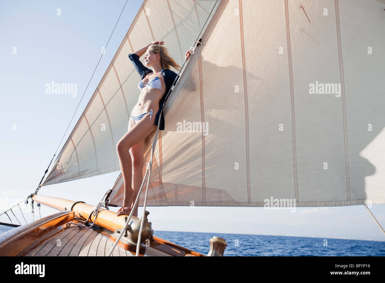 woman leaning at the sails of a boat - Stock Image