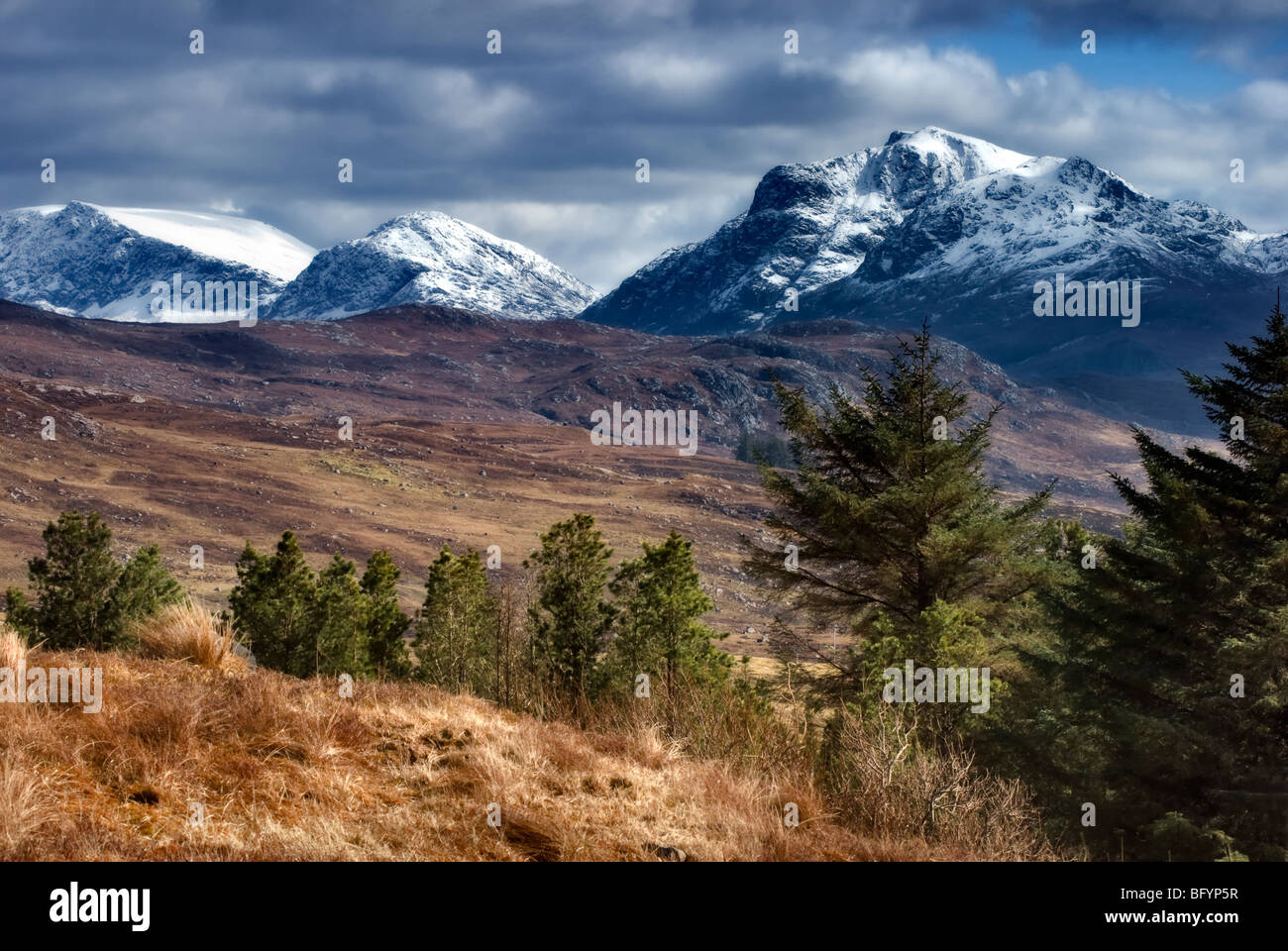 Snowy mountain scene taken from just oustide Poolewe on A832 looking towards mountains that flank Loch Maree in - Stock Image