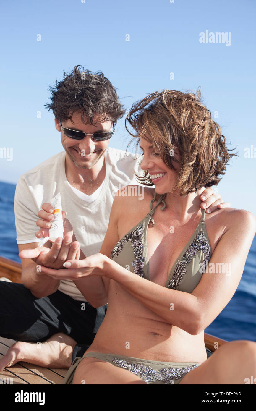 couple laughing applying suntan lotion - Stock Image