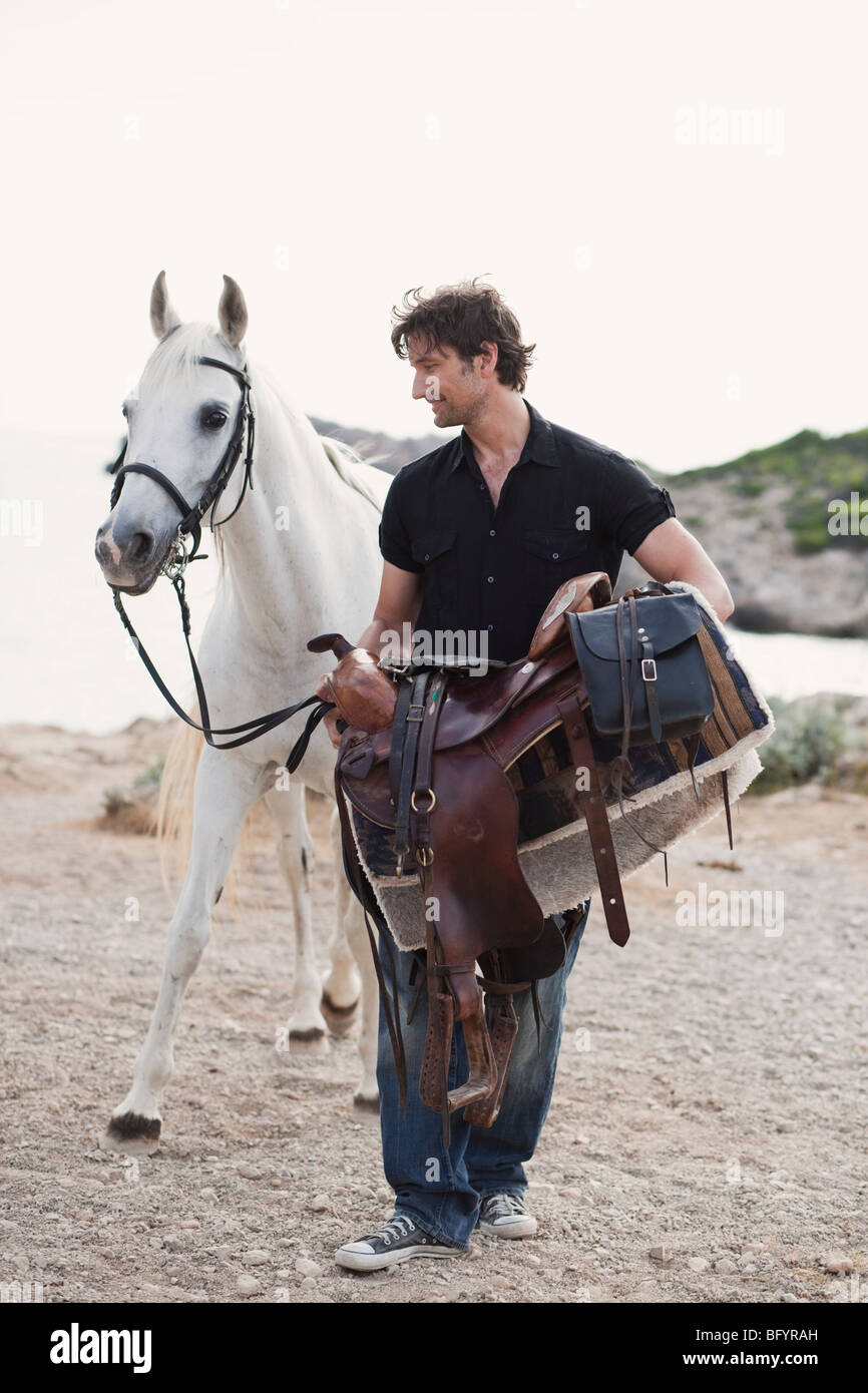 man carrying horses saddle - Stock Image