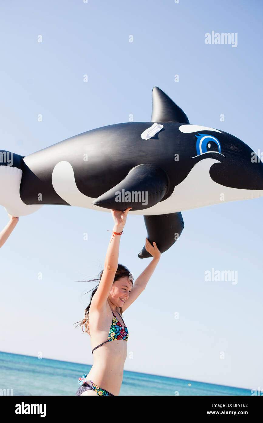 young girl carrying toy whale - Stock Image