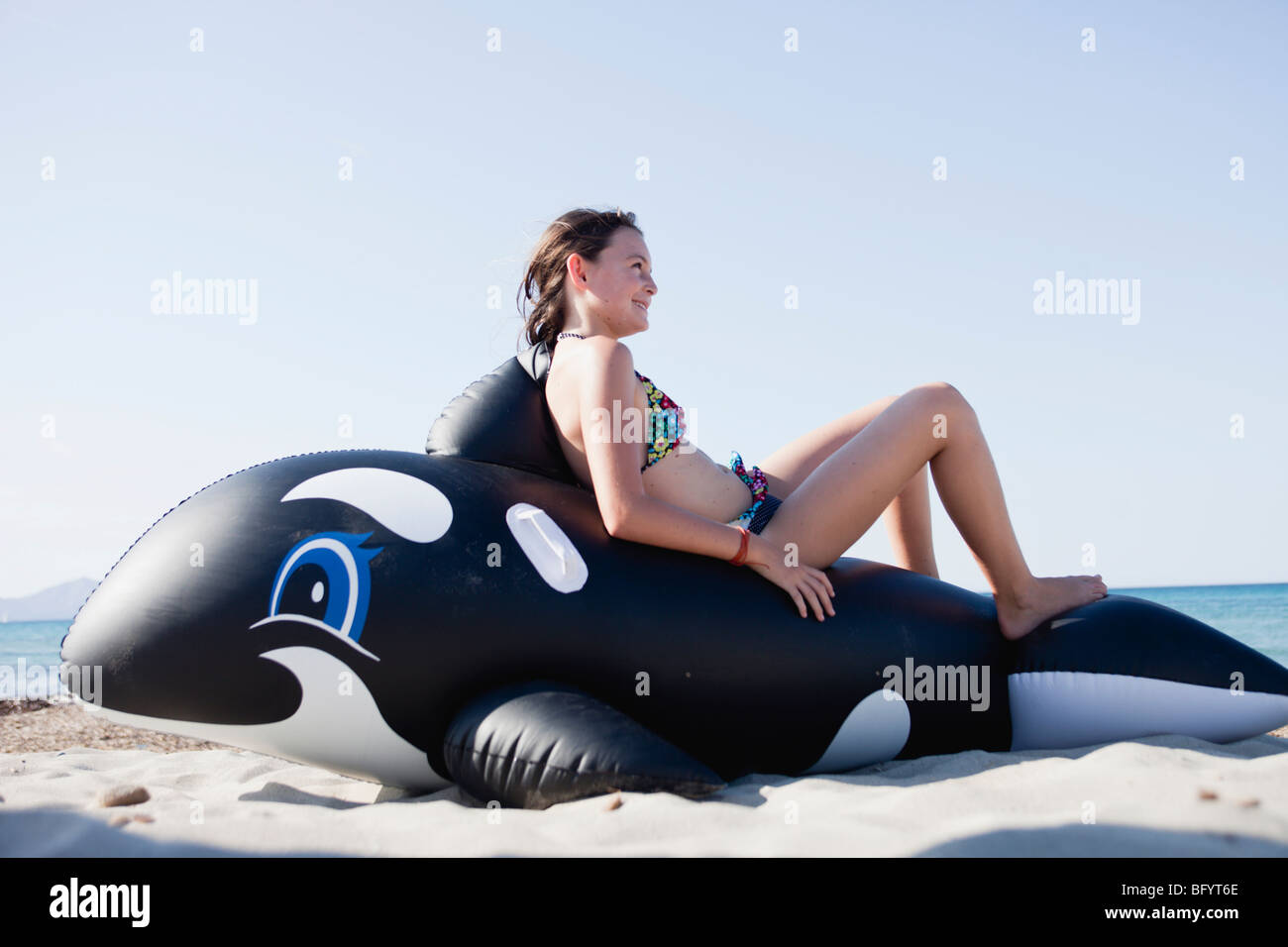 young girl sitting on toy whale - Stock Image