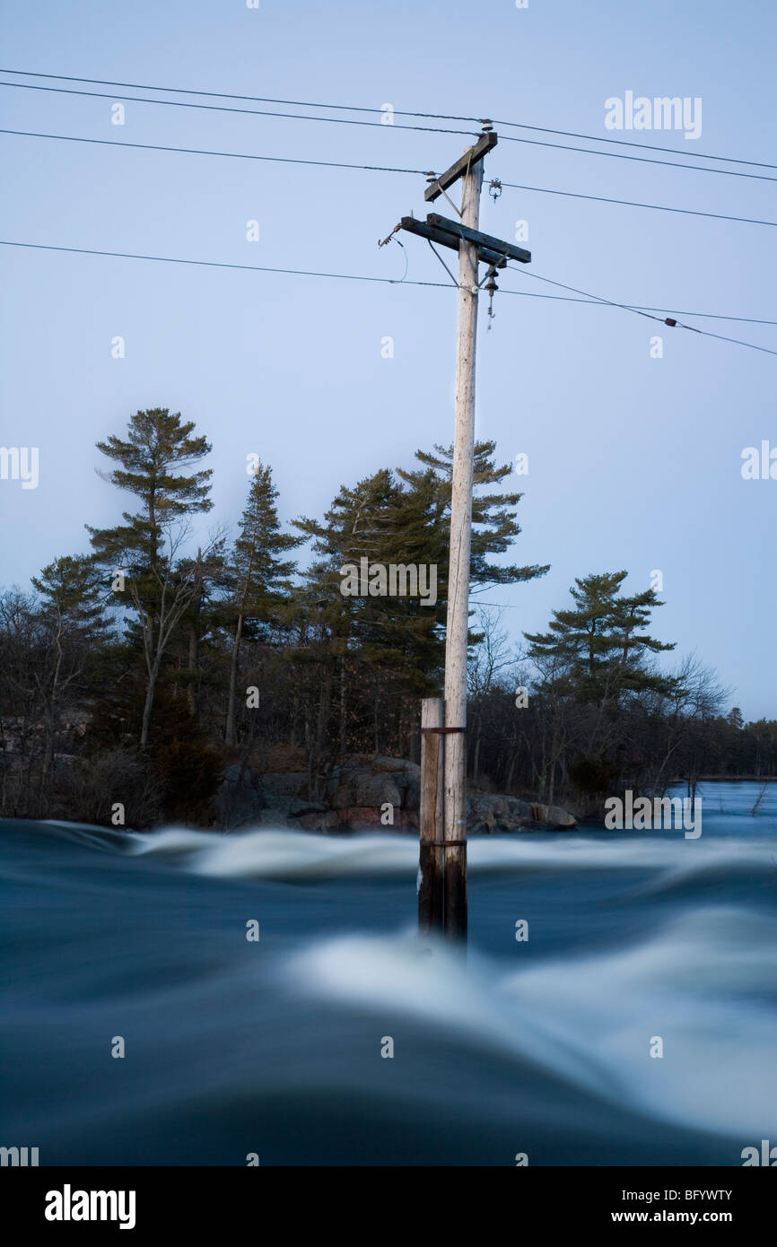Electricity pole submerged by flood - Stock Image