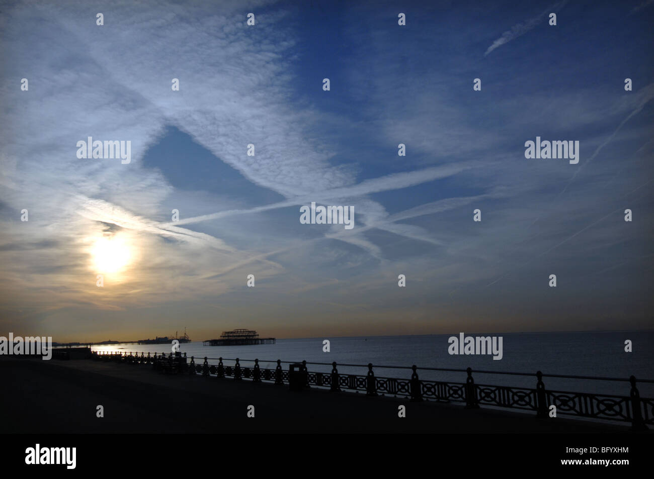 Sunrise on Brighton seafront with jet streaks in sky and the West Pier  silhouetted in the distance. - Stock Image